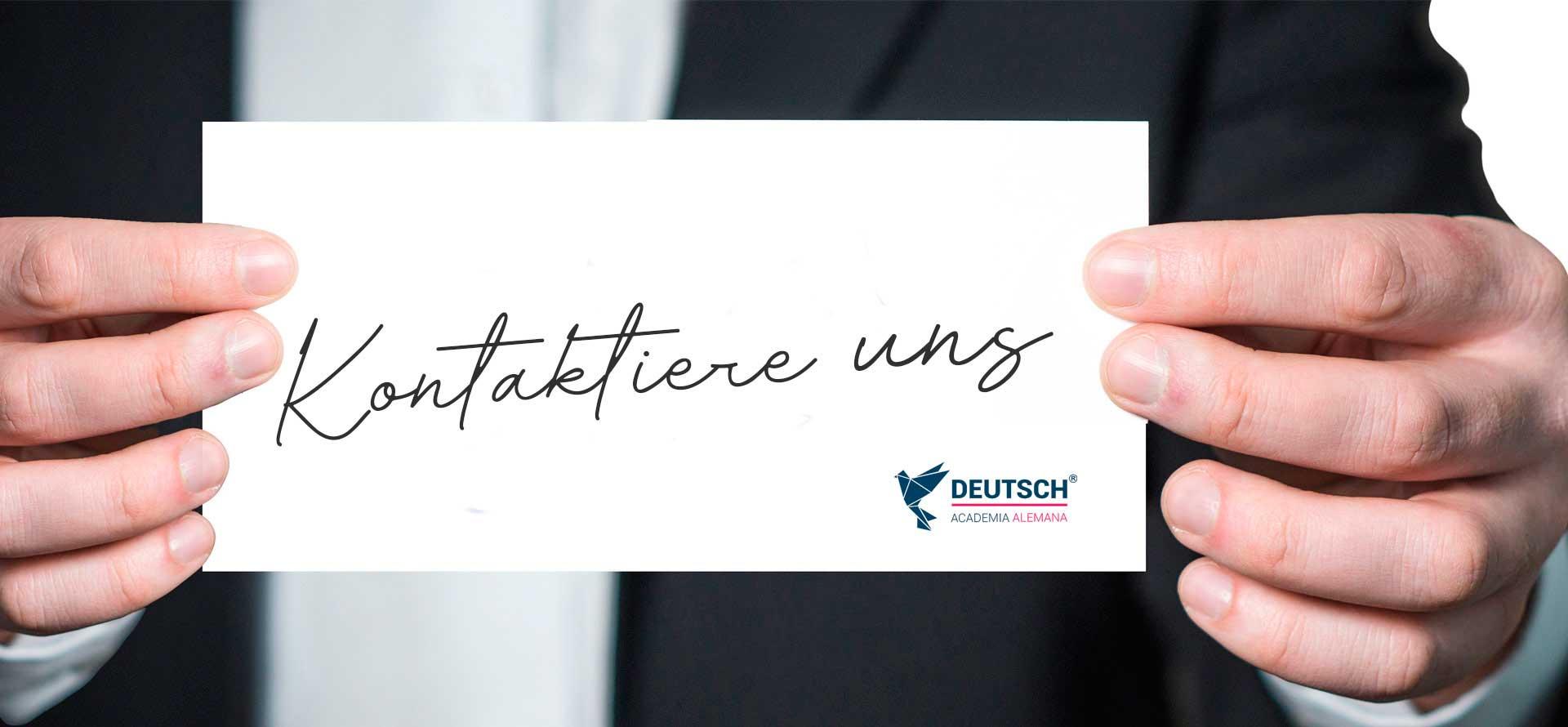 """Imagen panorámica que muestra una persona con una cartelera que dice """"Contáctanos"""" en Alemán"""